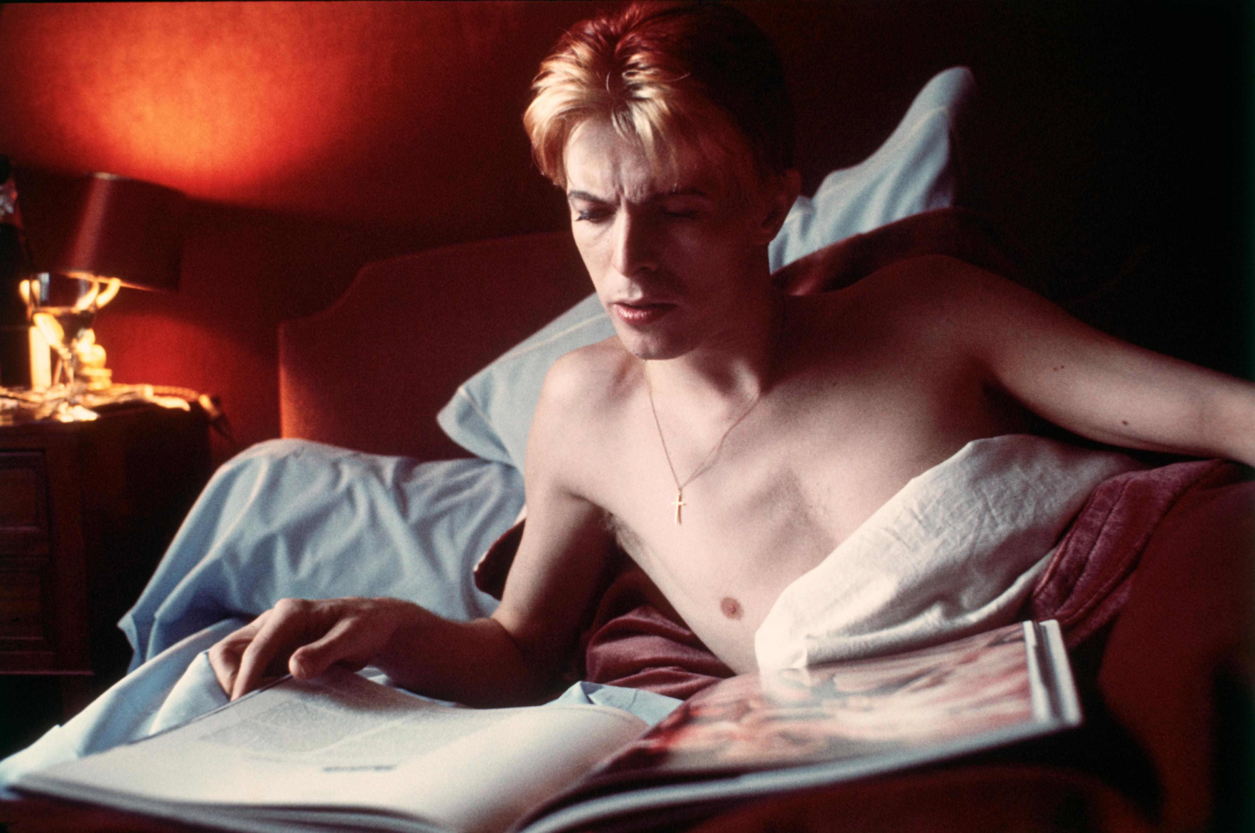 David Bowie reads a book in his bed during a rare quiet moment in his suite at L'Hotel in Paris in 1976