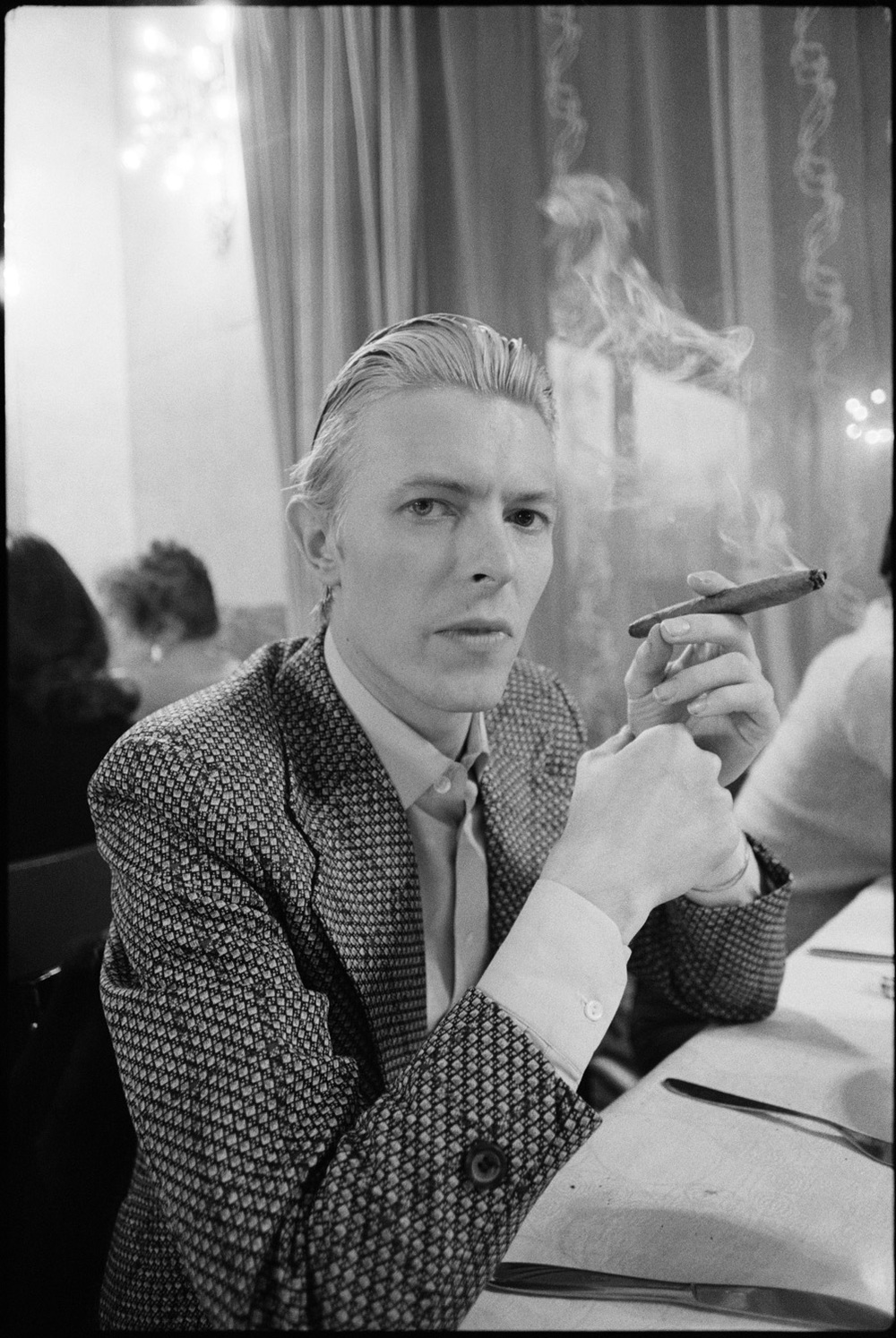 David Bowie smoking a cigar at a table at the Metropole Hotel in Moscow 1976