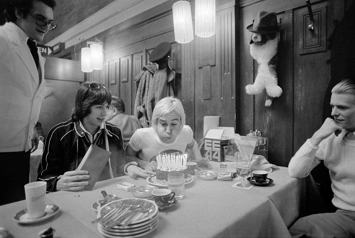 Iggy Pop blows out the candles on his birthday cake as David Bowie and tour manager Pat Gibbons look on at a restaurant in Basel Switzerland 1976