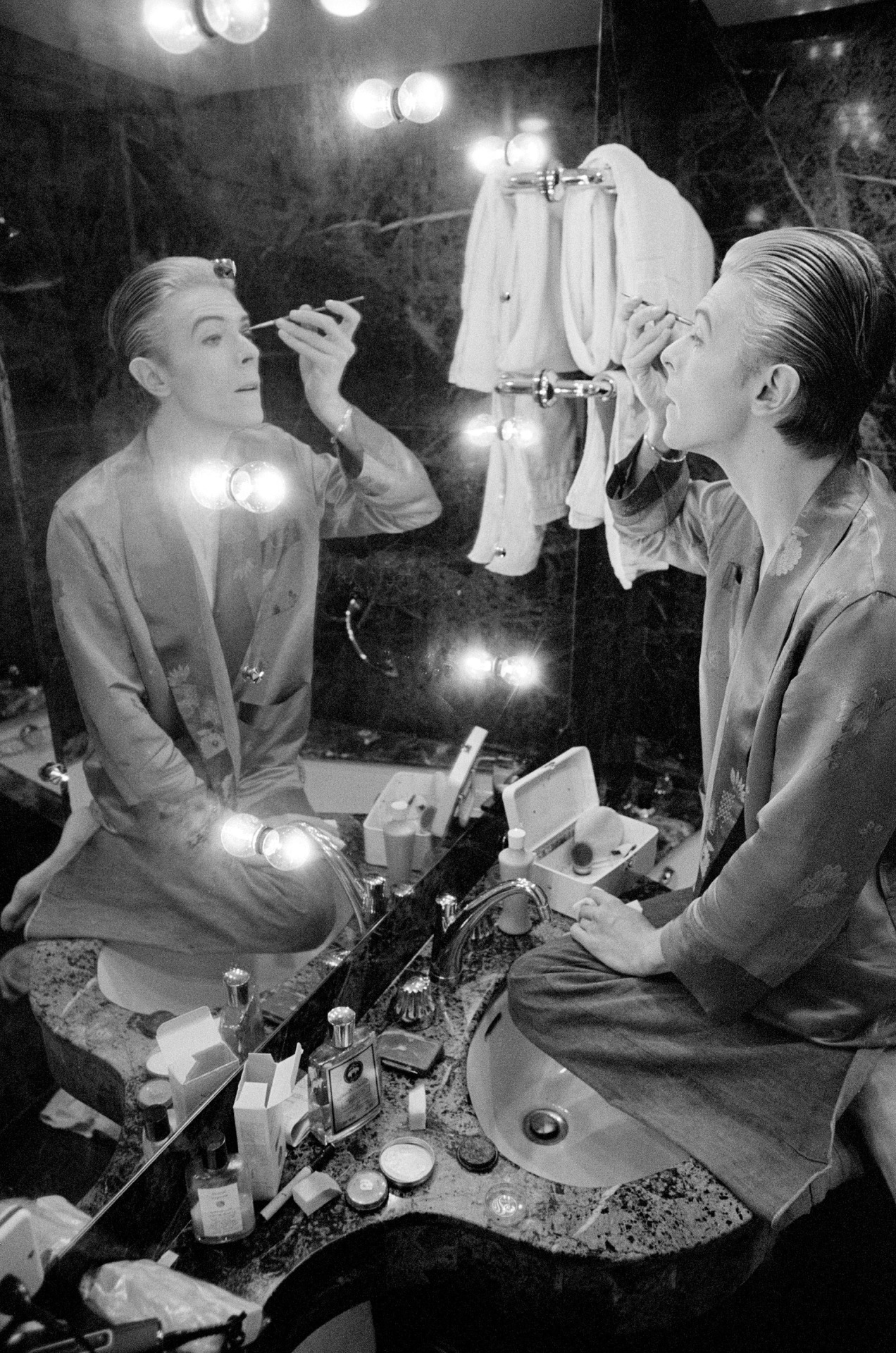David Bowie prepares his make-up at L'Hotel in Paris ahead of photo shoot in 1976