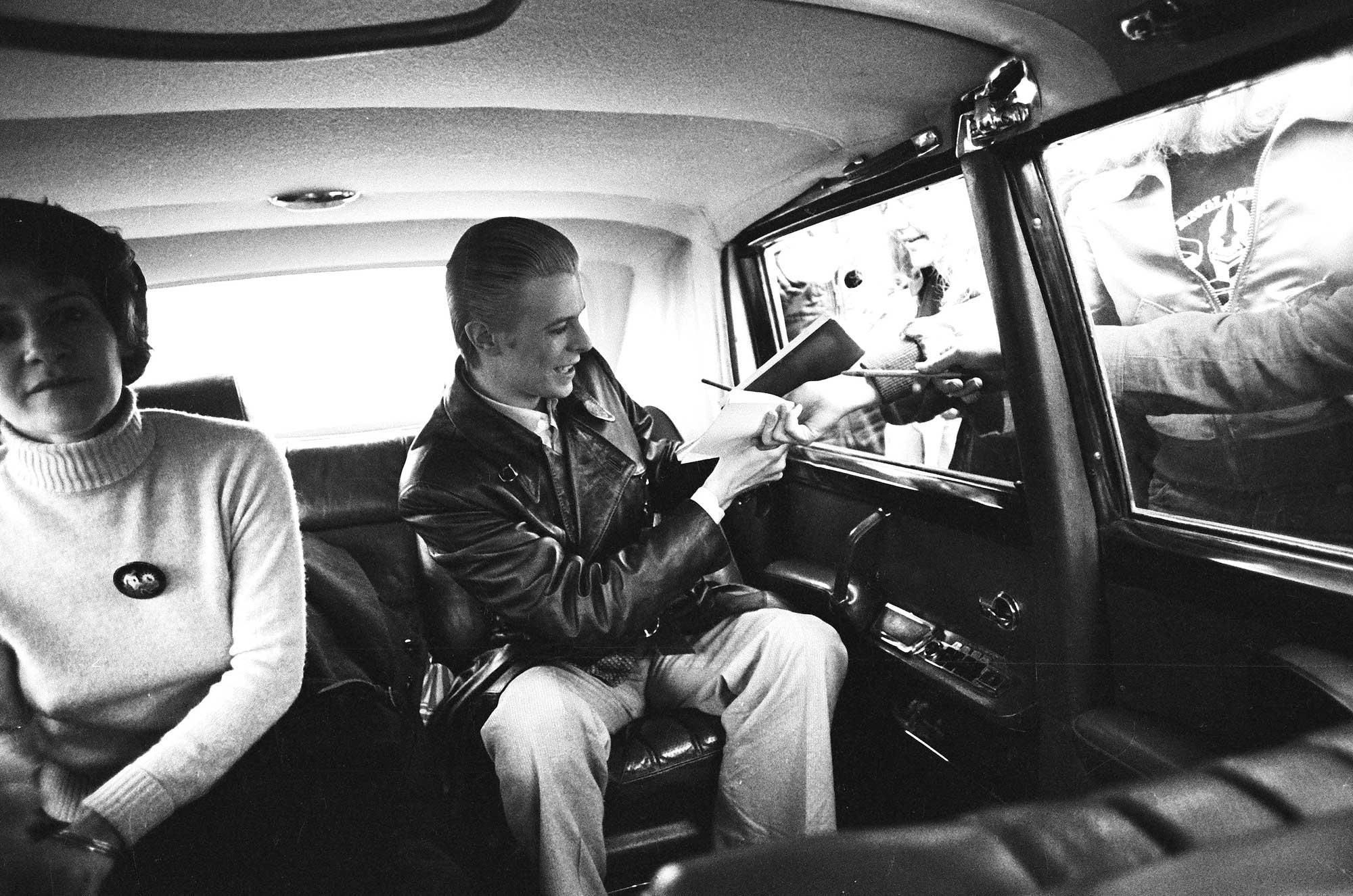 David Bowie signs an autograph in the back of his limousine 1976